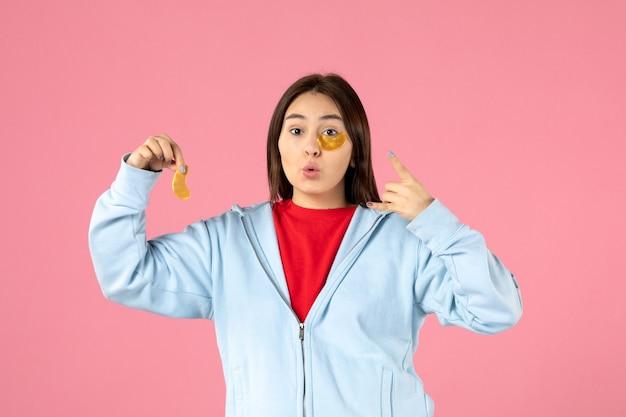 Vue de face d'une jeune femme faisant un masque facial sur un mur rose