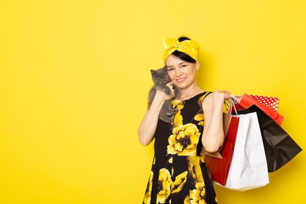 Une vue de face jeune femme en fleur jaune-noir robe conçue avec un bandage jaune sur la tête tenant des colis et chaton sur le jaune