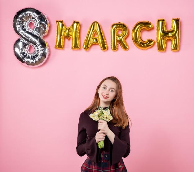 Vue de face jeune femme avec des fleurs dans ses mains et décoration de mars sur fond rose fête jour de la femme mars mariage passion présente l'égalité