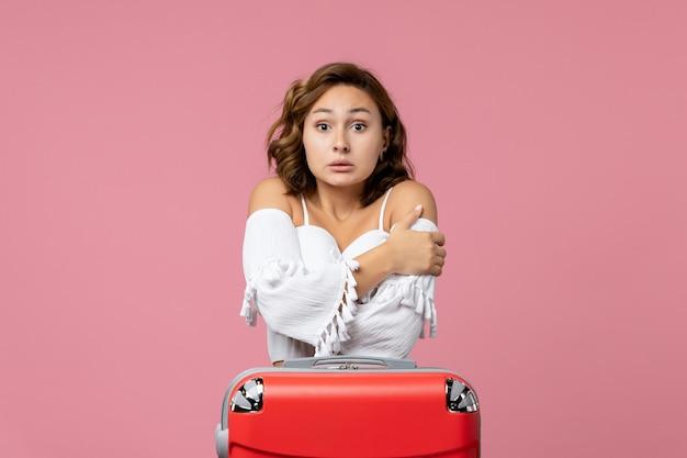 Vue de face d'une jeune femme grelottant de froid sur un mur rose