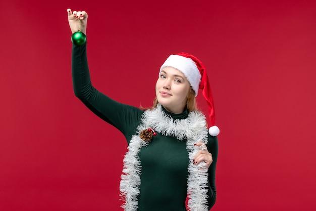 Vue de face jeune femme avec des guirlandes et de l'humeur du nouvel an sur fond rouge