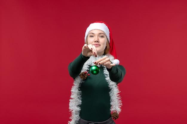 Vue de face jeune femme avec des guirlandes tenant le jouet sur le fond rouge