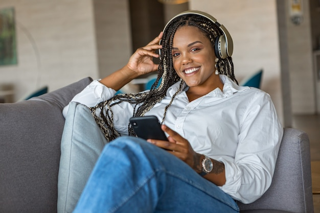 Vue de face d'une jeune femme heureuse écoutant de la musique avec des écouteurs et utilisant un téléphone portable tout en s'appuyant sur un canapé à la maison en regardant la caméra. concept de personnes à la maison.
