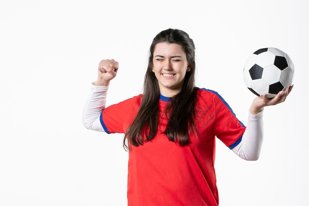 Vue de face jeune femme heureuse en vêtements de sport avec ballon de foot