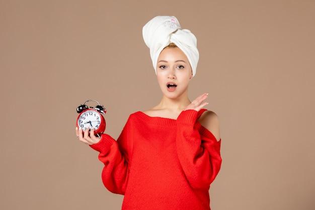 Vue de face jeune femme avec horloge et serviette sur sa tête sur fond rose
