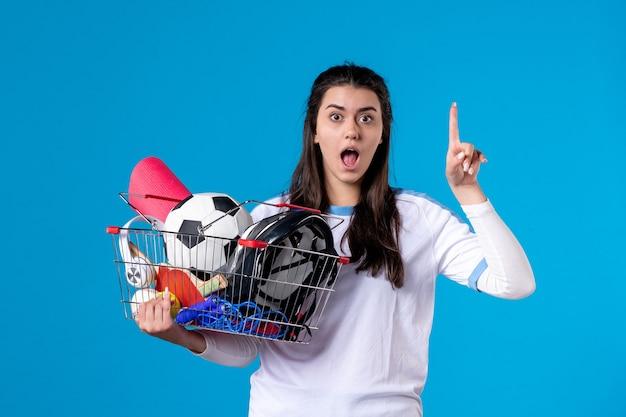 Vue de face jeune femme a une idée avec panier plein de choses de sport mur bleu