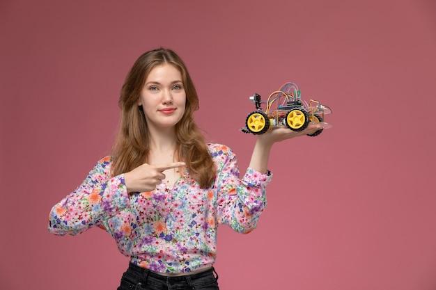 Vue de face jeune femme illustre jouet voiture