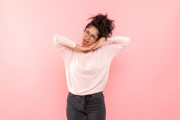 Vue de face de la jeune femme imitant dormir sur le mur rose