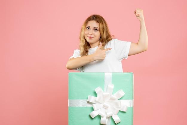 Vue de face jeune femme à l'intérieur de la boîte cadeau bleu flexing