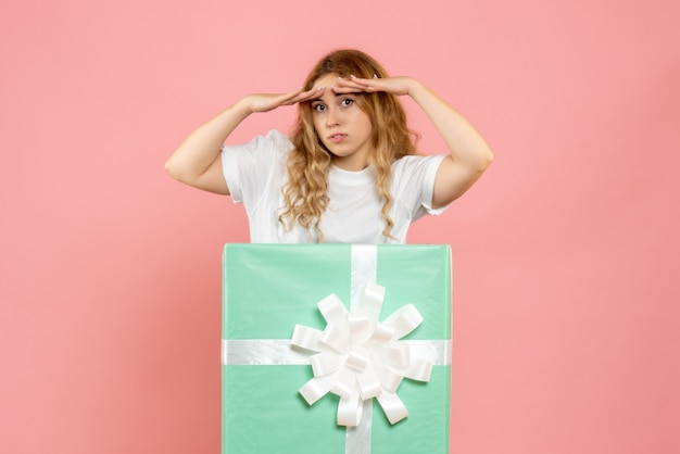 Vue de face jeune femme à l'intérieur de la boîte cadeau bleue