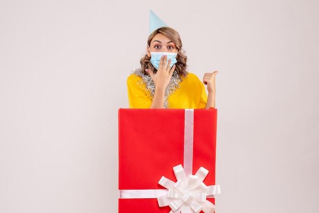 Vue de face jeune femme à l'intérieur de la boîte cadeau rouge en masque