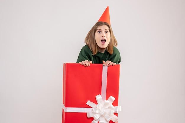 Vue de face jeune femme à l'intérieur de la boîte cadeau rouge