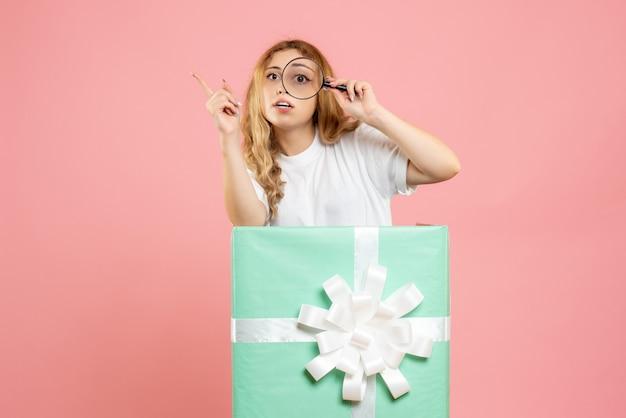 Vue de face jeune femme à l'intérieur de la boîte présente bleu à l'aide de la loupe