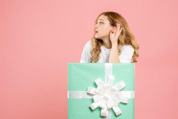 Vue de face jeune femme à l'intérieur de la boîte présente bleu écoute