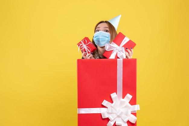 Vue de face jeune femme à l'intérieur de la boîte présente en masque stérile avec cadeau