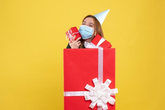 Vue de face jeune femme à l'intérieur de la boîte présente en masque stérile avec des cadeaux