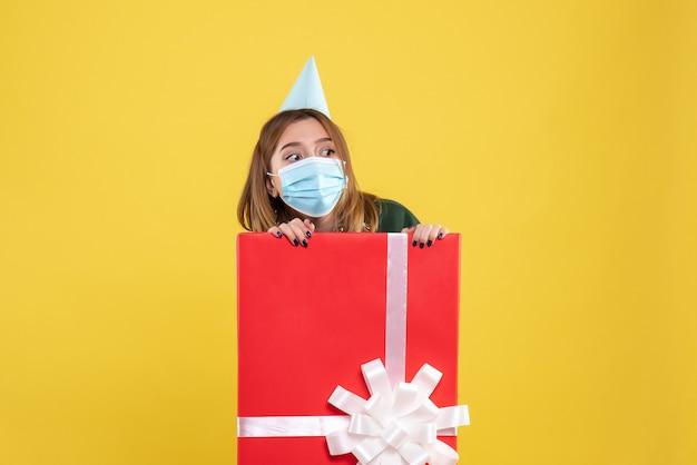 Vue de face jeune femme à l'intérieur de la boîte présente en masque stérile
