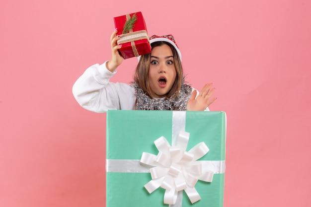 Vue de face de la jeune femme à l'intérieur de la boîte présente tenant peu de cadeau sur le mur rose