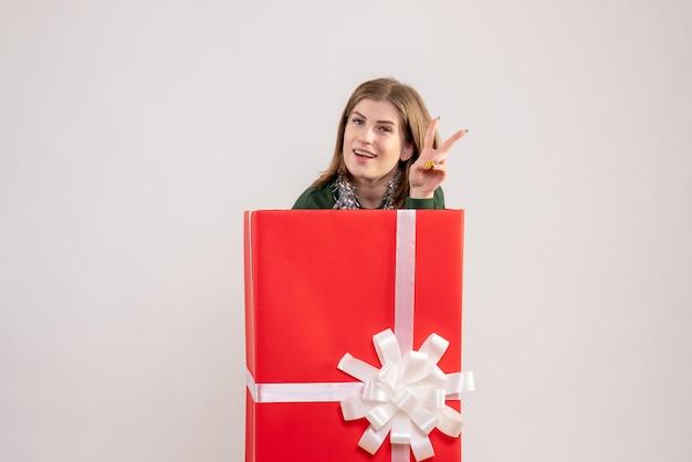 Vue de face jeune femme à l'intérieur de la boîte présente
