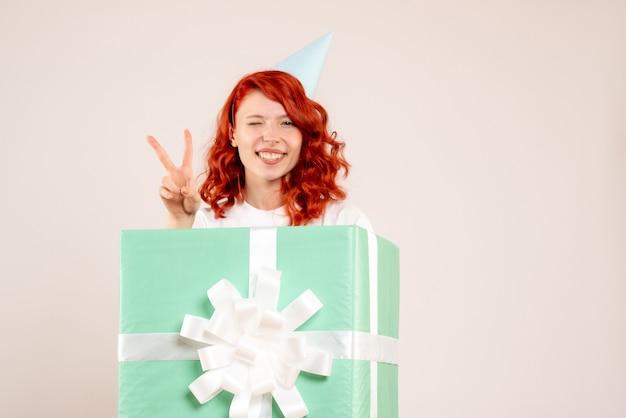 Vue de face jeune femme à l'intérieur présent sur plancher blanc cadeau noël photo émotion nouvel an