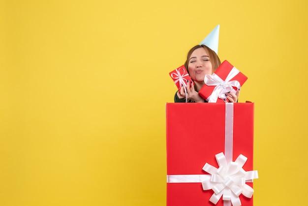 Vue de face jeune femme à l'intérieur présente avec des cadeaux