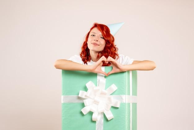 Vue de face jeune femme à l'intérieur présente l'envoi d'amour sur fond blanc