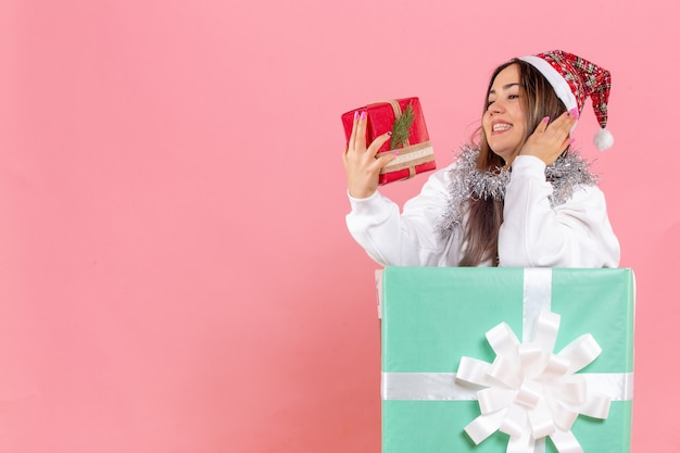 Vue de face de la jeune femme à l'intérieur présente tenant un autre cadeau sur le mur rose