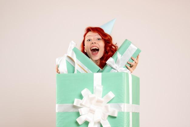 Vue de face jeune femme à l'intérieur présente tenant d'autres cadeaux sur fond blanc