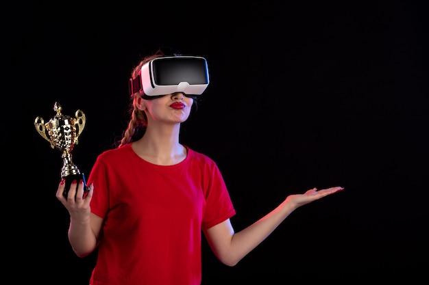 Vue de face d'une jeune femme jouant au vr avec la coupe du vainqueur sur un jeu de technologie visuelle d'un bureau sombre