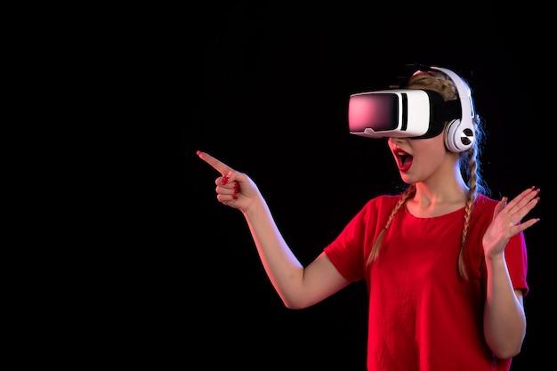 Vue de face d'une jeune femme jouant au vr dans les écouteurs dans l'obscurité