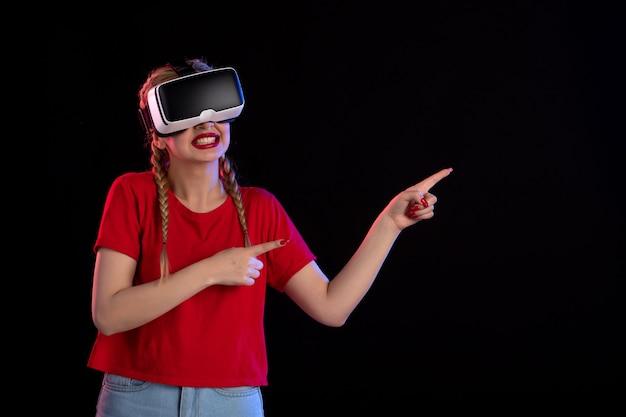Vue de face d'une jeune femme jouant au vr sur un mur sombre