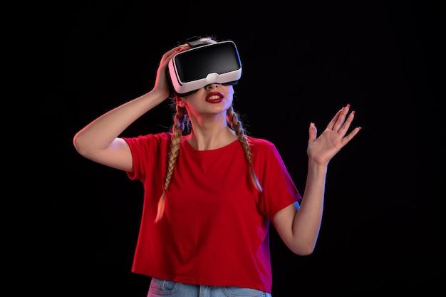 Vue de face d'une jeune femme jouant à la réalité virtuelle sur une échographie visuelle de technologie sombre