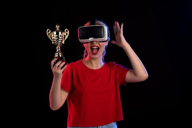 Vue de face d'une jeune femme jouant à la réalité virtuelle et gagnant la coupe sur un mur sombre