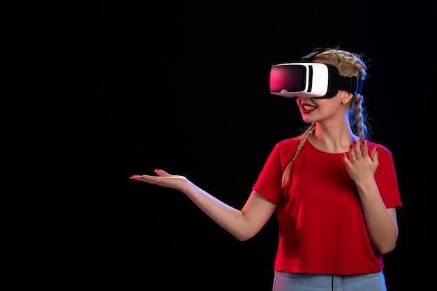 Vue de face d'une jeune femme jouant à la réalité virtuelle sur un jeu de fantaisie visuelle sombre