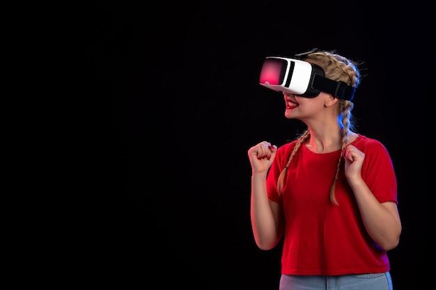 Vue de face d'une jeune femme jouant à la réalité virtuelle sur le jeu visuel sombre.