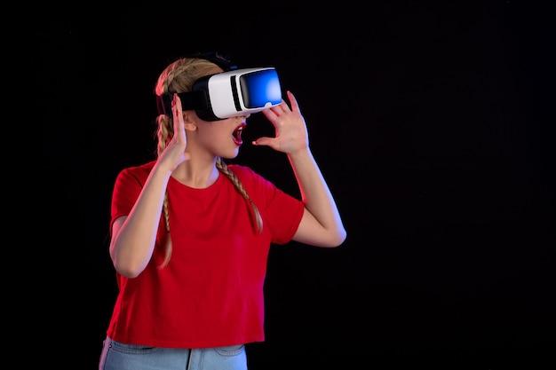 Vue de face d'une jeune femme jouant à la réalité virtuelle sur un jeu visuel à ultrasons sombre