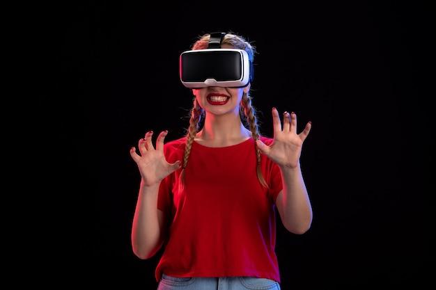 Vue de face d'une jeune femme jouant à la réalité virtuelle sur un mur sombre