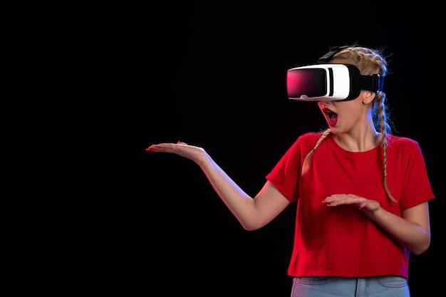 Vue de face d'une jeune femme jouant à la réalité virtuelle sur une technologie d'échographie visuelle de jeu sombre
