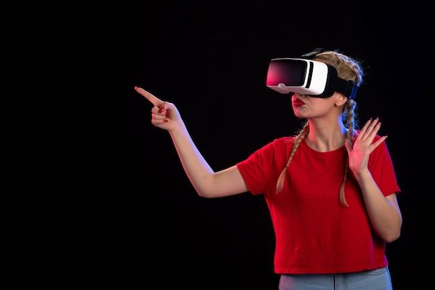 Vue de face d'une jeune femme jouant à la réalité virtuelle sur un visuel échographique de technologie de jeu sombre