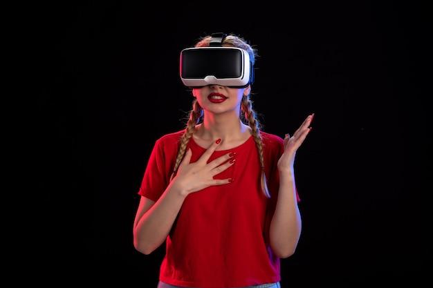 Vue de face d'une jeune femme jouant à la réalité virtuelle sur un visuel sombre