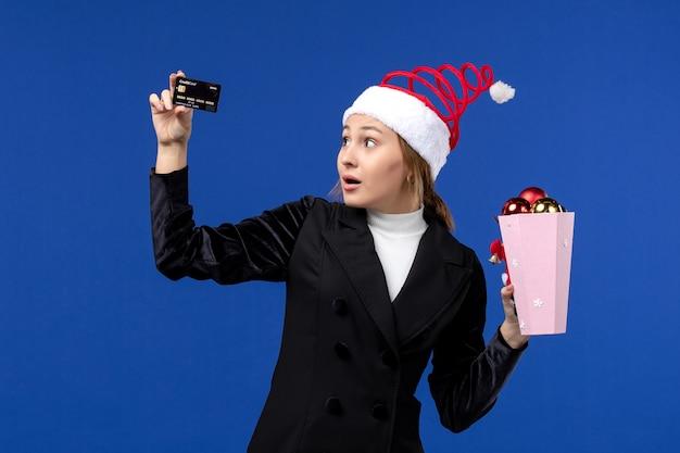 Vue de face jeune femme avec des jouets d'arbre et carte bancaire sur le bureau bleu émotion vacances de nouvel an
