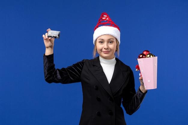 Vue de face jeune femme avec des jouets d'arbre et carte bancaire sur le mur bleu émotion vacances de nouvel an