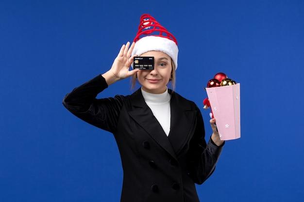 Vue de face jeune femme avec des jouets d'arbre et carte bancaire sur le mur bleu émotions vacances de nouvel an