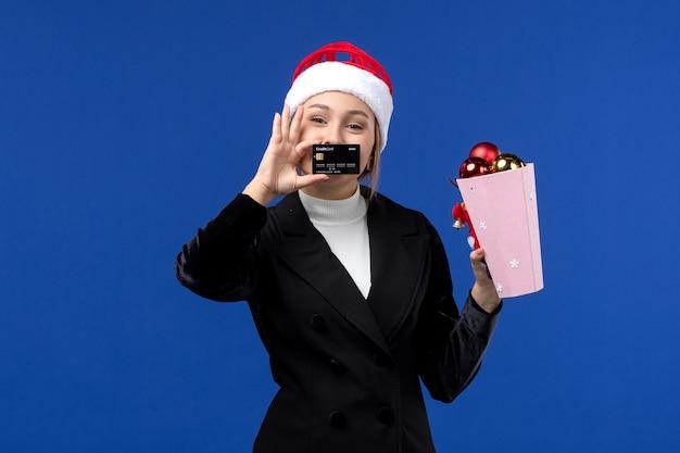 Vue de face jeune femme avec des jouets d'arbre et carte bancaire sur mur bleu vacances nouvel an émotion
