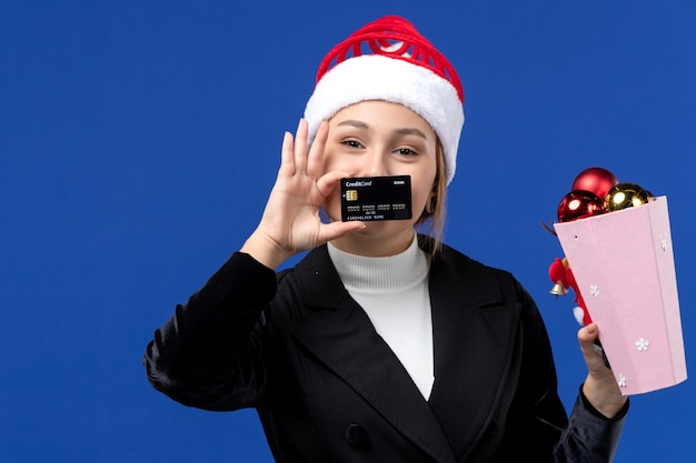 Vue de face jeune femme avec des jouets d'arbre et carte bancaire sur le mur bleu vacances de nouvel an émotions