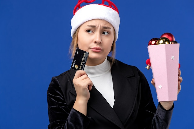 Vue de face jeune femme avec des jouets d'arbre et carte bancaire sur plancher bleu vacances nouvel an émotion