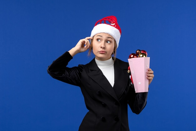 Vue de face jeune femme avec des jouets d'arbre sur le mur bleu émotion jouet de vacances de nouvel an