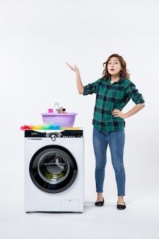 Vue de face de la jeune femme avec lave-linge sur mur blanc
