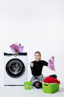 Vue de face d'une jeune femme avec une machine à laver pliant des vêtements sales sur un mur blanc