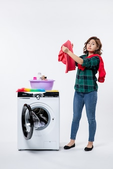 Vue de face d'une jeune femme avec une machine à laver préparant des vêtements pour le lavage sur un mur clair